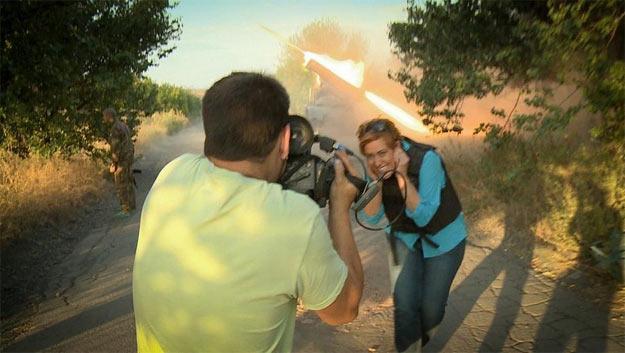 """Журналістка Russia Today усміхаючись позує на фоні стріляючого """"Граду"""""""